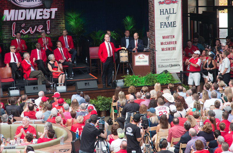 Top row left: Jim Edmonds, Ted Simmons, Chris Carpenter. Second row: Whitey Herzog, Bob Gibson, Tony LaRussa. Front row: Tim McCarver, Jenny Weathersby (daughter of Pepper Martin) .  Standing with plaque is Mark McGwire. with Bill DeWitt, Jr, GM John Mozelak, Bill DeWitt, Sr, and Emcee/broadcaster Dan McLaughlin -- Cardinals Hall of Fame Induction ceremony 2017, Ballpark Village, St. Louis, Aug 26, 2017.