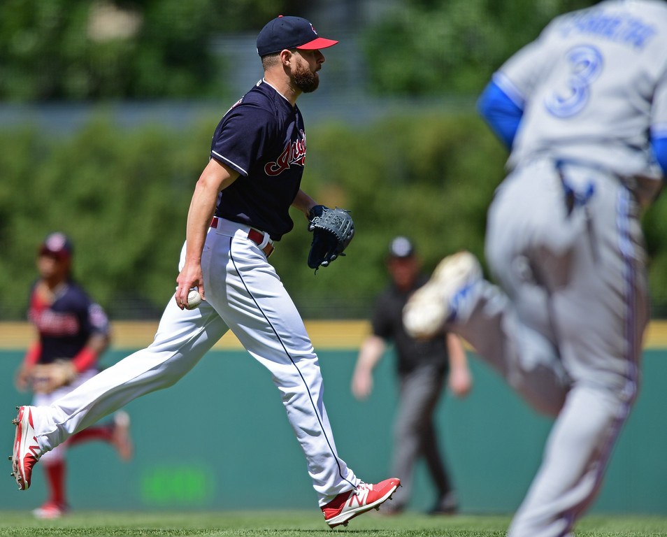 . Cleveland Indians starting pitcher Corey Kluber underhands the ball to put out Toronto Blue Jays\' Ezequiel Carrera in the fifth inning of a baseball game, Sunday, Aug. 21, 2016, in Cleveland. (AP Photo/David Dermer)