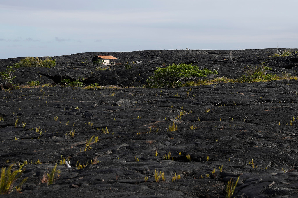 . A structure is seen atop the 1990 lava flow, Sunday, May 6, 2018, in Kalapana, Hawaii. (AP Photo/Marco Garcia)