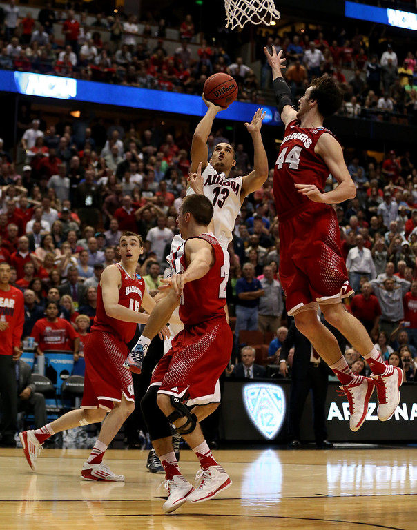 . Nick Johnson #13 of the Arizona Wildcats is called for an offense foul as he drives on Josh Gasser #21 of the Wisconsin Badgers in overtime during the West Regional Final of the 2014 NCAA Men\'s Basketball Tournament at the Honda Center on March 29, 2014 in Anaheim, California.  (Photo by Jeff Gross/Getty Images)