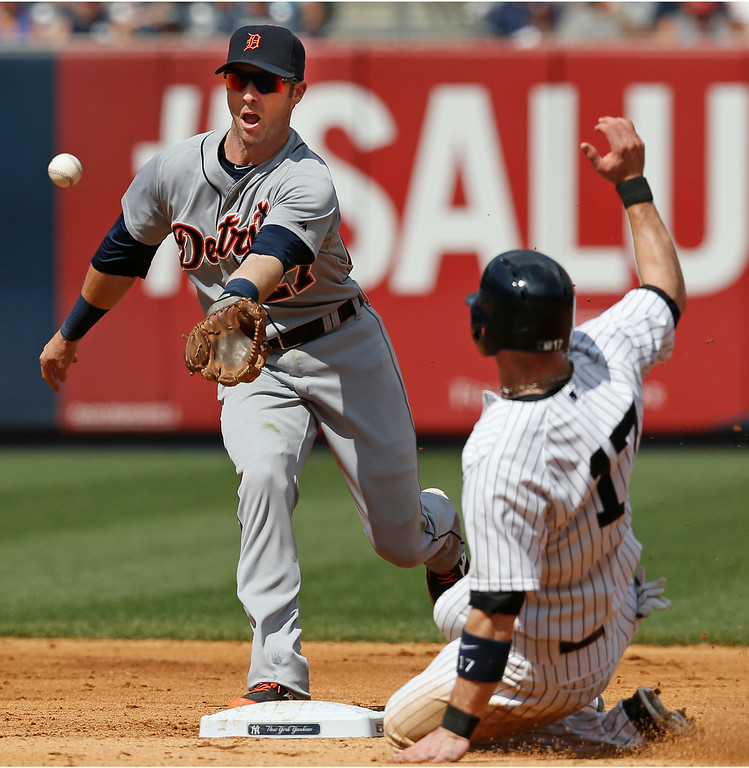 . Detroit Tigers shortstop Andrew Romine reacts as he fields Brett Gardner\'s seventh-inning ground ball single that loaded the bases, as New York Yankees\' Brendan Ryan slides into second in a baseball game at Yankee Stadium in New York, Thursday, Aug. 7, 2014.   (AP Photo/Kathy Willens)