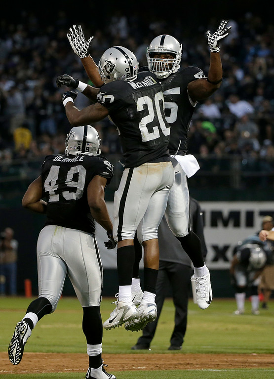 . Oakland Raiders running back Darren McFadden (20) celebrates after scoring on a 1-yard touchdown run with fullback Marcel Reece during the second quarter of an NFL preseason football game against the Detroit Lions in Oakland, Calif., Friday, Aug. 15, 2014. (AP Photo/Marcio Jose Sanchez)