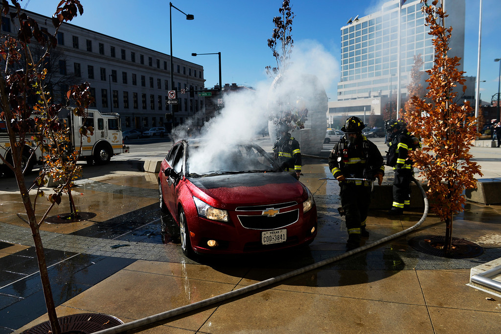 . Denver Fire works on putting out a car fire outside the Wellington Webb Building, November 07, 2013. The car was on fire parked in the middle of the building plaza walkway in downtown Denver. (Photo By RJ Sangosti/The Denver Post)