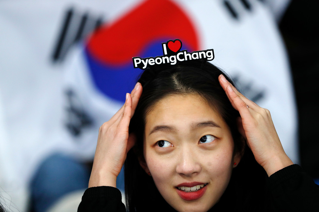 """. A fan of South Korea\'s speedskaters adjust her headband which reads \""""I Love PyeongChang\"""" as she waits for the start of the men\'s 1,500 meters speedskating race at the Gangneung Oval at the 2018 Winter Olympics in Gangneung, South Korea, Tuesday, Feb. 13, 2018. (AP Photo/John Locher)"""