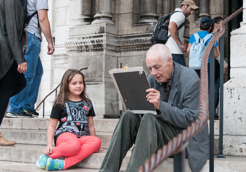 Artist drawing a portrait on the stairs of Sacre-Coeur