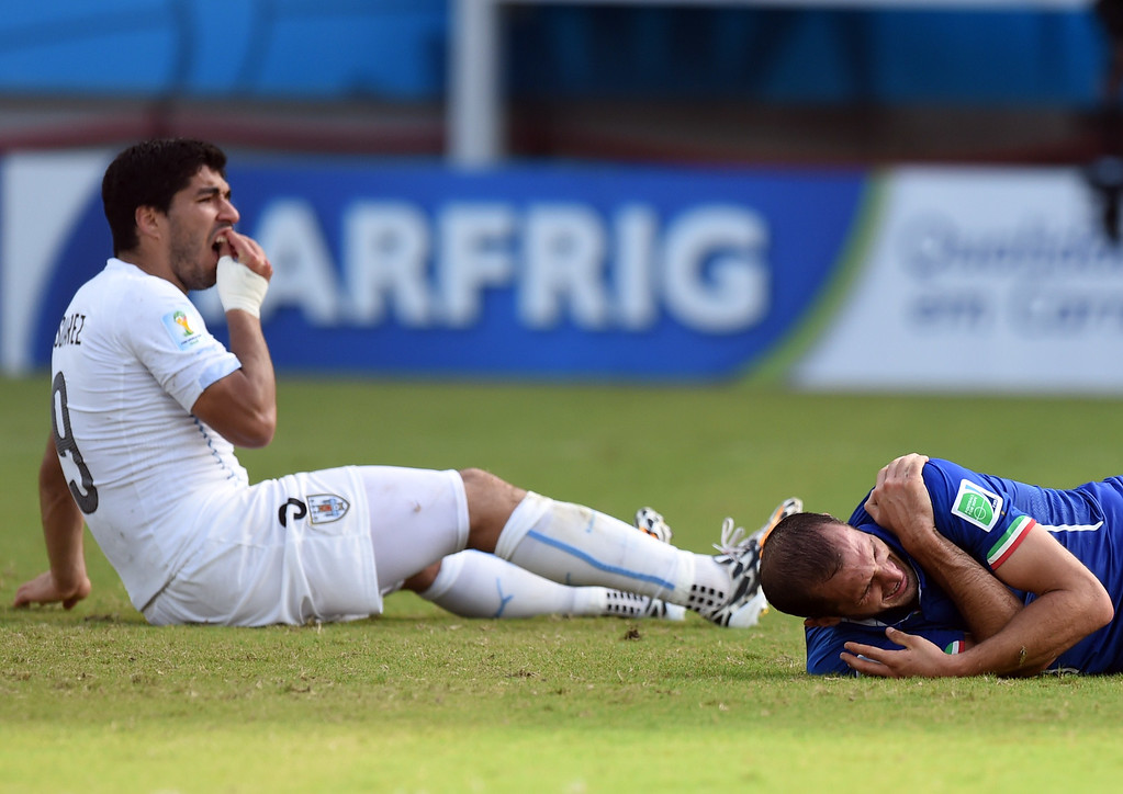 . Uruguay\'s forward Luis Suarez (L) reacts past Italy\'s defender Giorgio Chiellini during a Group D football match between Italy and Uruguay at the Dunas Arena in Natal during the 2014 FIFA World Cup on June 24, 2014.   AFP PHOTO/ JAVIER  SORIANO/AFP/Getty Images