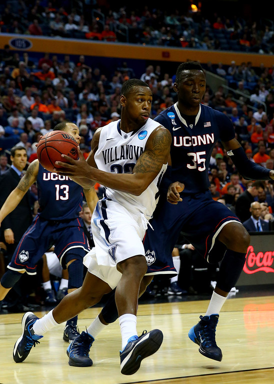 . BUFFALO, NY - MARCH 22: James Bell #32 of the Villanova Wildcats drives to the basket as Amida Brimah #35 of the Connecticut Huskies defends during the third round of the 2014 NCAA Men\'s Basketball Tournament at the First Niagara Center on March 22, 2014 in Buffalo, New York.  (Photo by Elsa/Getty Images)