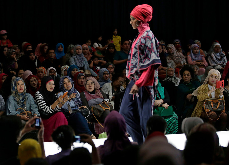 . In this Saturday, May 31, 2013 photo, Muslim women react as a model showcases a creation by Indonesian designer Najua Yanti during the Islamic Fashion Fair in Jakarta, Indonesia. The event is part of the Indonesian government\'s effort to turn the most populous Muslim country into the world\'s Islamic fashion capital by 2020. (AP Photo/Dita Alangkara)