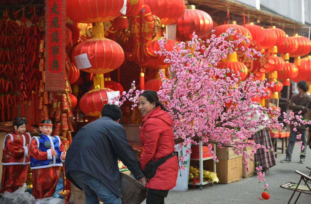 . A couple carry a cherry blossom tree at a Chinese New Year street fair on the eve of the holiday in Shanghai on January 30, 2014. AFP PHOTO/Peter PARKS/AFP/Getty Images