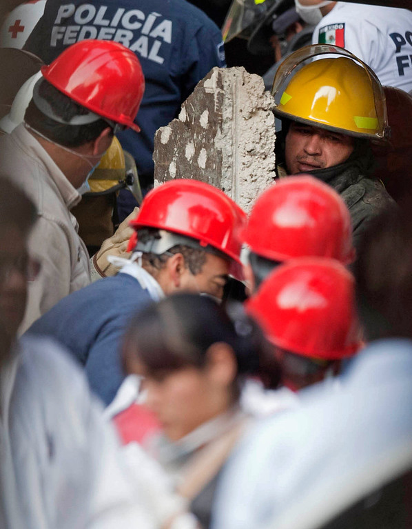 . An emergency responder carries a piece of concrete as emergency workers and firefighter dig for survivor at the site on an explosion at an adjacent building to the executive tower of Mexico\'s state-owned oil company PEMEX, in Mexico City, Thursday Jan. 31, 2013.    (AP Photo/Eduardo Verdugo)