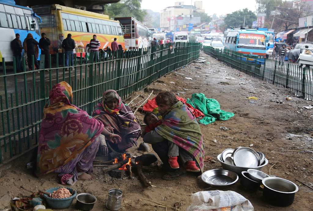 . Homeless Indians sit around a bonfire to keep warm under a flyover on a cold winters day in Jammu, India, Saturday, Jan. 7, 2017. Some 800 million people in the country live in poverty, many of them migrating to big cities in search of a livelihood and often ending up on the streets. (AP Photo/Channi Anand)