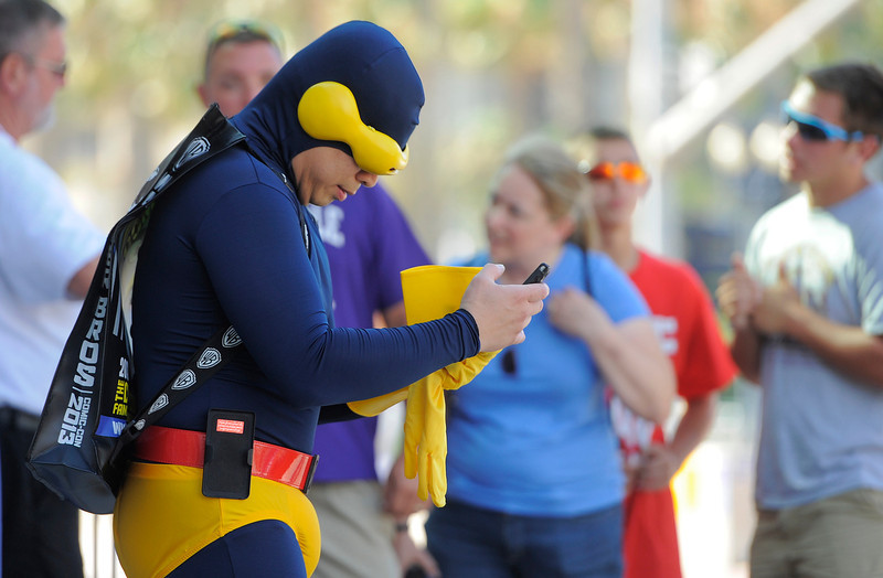 """. Gene Ross, left, of Chula Vista, Calif., dressed as \""""Cyclops,\"""" checks his cell phone as he stands outside the 2013 Comic-Con International Convention on Wednesday, July 17, 2013 in San Diego, Calif. (Photo by Chris Pizzello/Invision/AP)"""