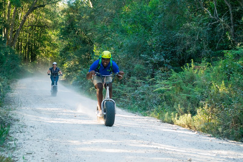 man racing through forest on one wheeled scooter