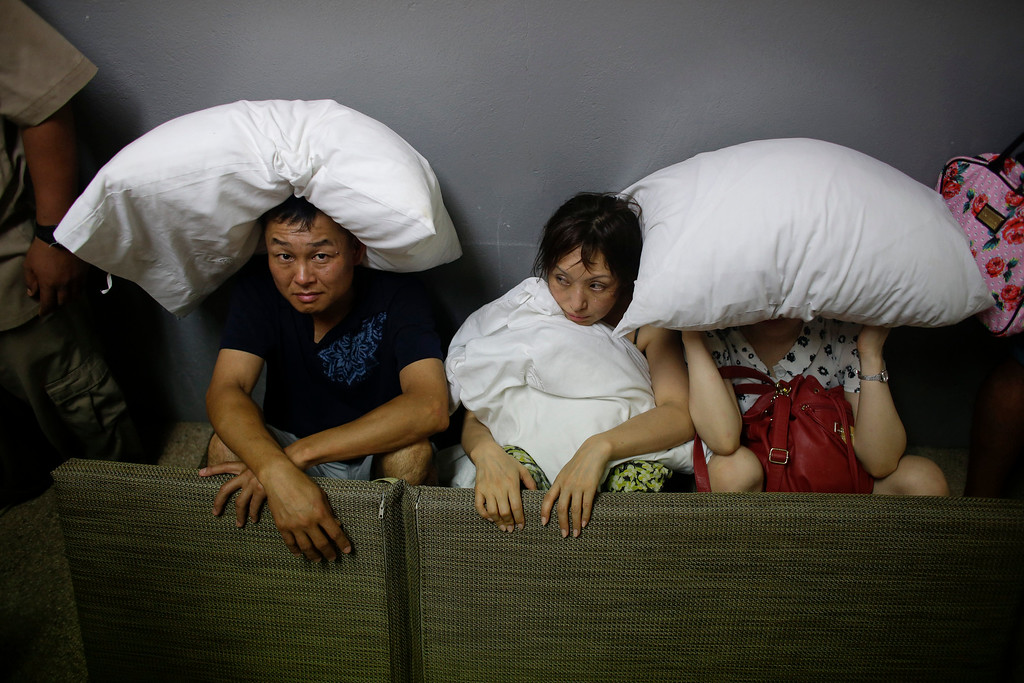 . A family from San Jose, California,  cover themselves with pillows as they sit on the concrete stairs in the service area of a resort  after the designated area for shelter was destroyed by winds  in Los Cabos, Mexico,  Monday, Sept. 15, 2014. Hurricane Odile raked the Baja California Peninsula with strong winds and heavy rains early Monday as locals and tourists in the resort area of Los Cabos began to emerge from shelters and assess the damage. (AP Photo/Victor R. Caivano)
