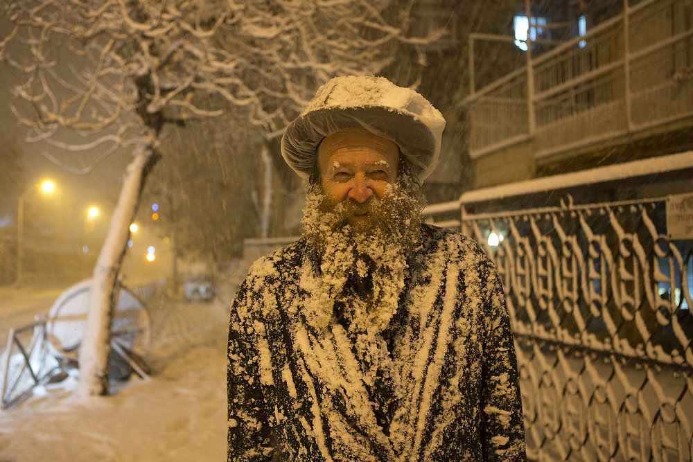 Description of . An Ultra-Orthodox Jewish man covered with snow walks in Jerusalem on January 10, 2013. Jerusalem was transformed into a winter wonderland after heavy overnight snowfall turned the Holy City and much of the region white, bringing hordes of excited children onto the streets. MENAHEM KAHANA/AFP/Getty Images