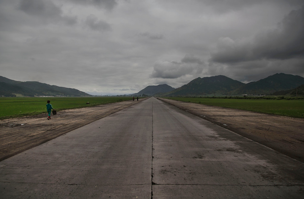 """. In this June 21, 2014 photo, a woman walks along an open road southeast of Pyongyang in North Korea\'s North Hwanghae province. The Associated Press was granted permission to embark on a weeklong road trip across North Korea to the countryís spiritual summit Mount Paektu. The trip was on North Korea\'s terms. An AP reporter and photographer couldn\'t interview ordinary people or wander off course, and government \""""minders\"""" accompanied them the entire way. (AP Photo/David Guttenfelder)"""
