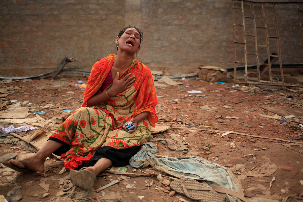 . A woman cries out for her missing husband at the site of the garment factory building that collapsed Wednesday, in Savar, near Dhaka, Bangladesh, Saturday, April 27, 2013. Police in Bangladesh took five people into custody in connection with the collapse of a shoddily-constructed building this week, as rescue workers pulled 19 survivors out of the rubble on Saturday and vowed to continue as long as necessary to find others despite fading hopes. (AP Photo/Wong Maye-E)