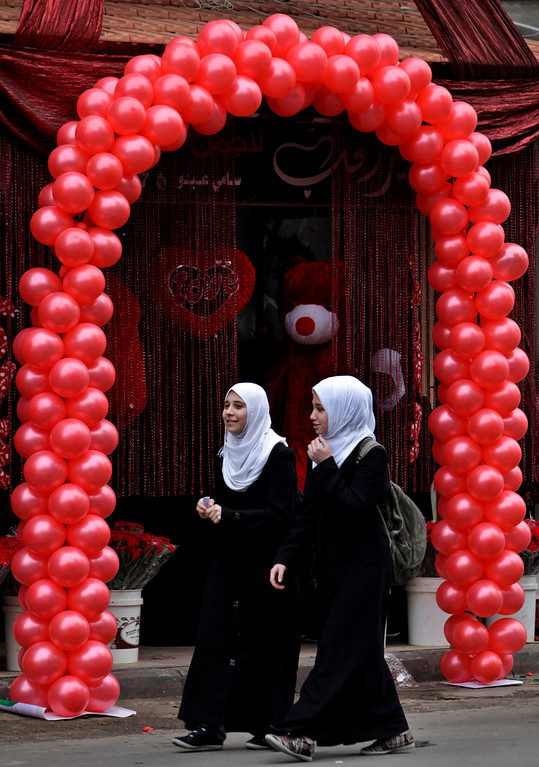 . Palestinian girls walk in front of a shop decorated for Valentine\'s Day, in Gaza City, Thursday, Feb. 14, 2013. Valentine\'s Day is a festival of romantic love and is celebrated in many countries over the world by giving cards, flowers or gifts to spouses or partners. (AP Photo/Adel Hana)