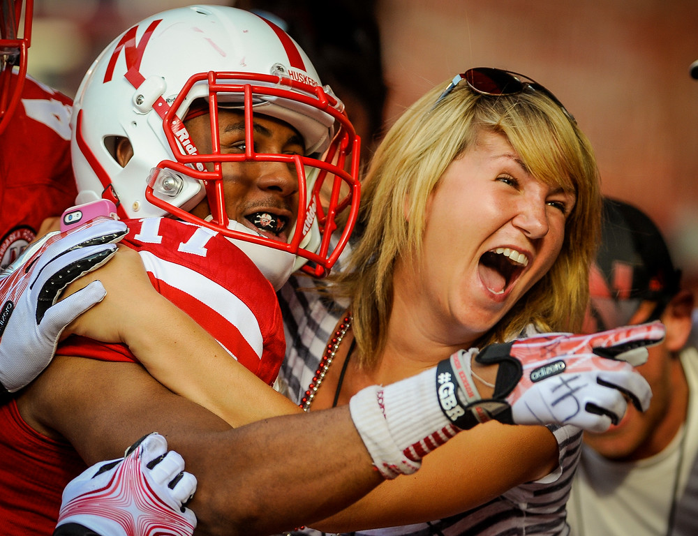 . LINCOLN, NE - SEPTEMBER 7: Jessica Klein gets a hug from cornerback Ciante Evans #17 of the Nebraska Cornhuskers after a pick six during their game Southern Miss Golden Eagles at Memorial Stadium on September 7, 2013 in Lincoln, Nebraska. (Photo by Eric Francis/Getty Images)