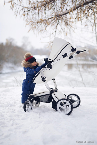 Mima_Xari_Lifestyle_Snow_White_Aluminium_Chassis_Pod_Baby_Looking_At_Pushchair_In_Snow_Zoomed_Out.jpg