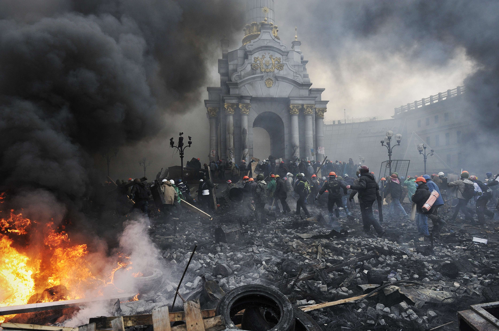 . Protesters advance towards new positions in Kiev on February 20, 2014. Armed protesters stormed police barricades in Kiev on Thursday in renewed violence that killed at least 26 people and shattered an hours-old truce as EU envoys held crisis talks with Ukraine\'s embattled president. Bodies of anti-government demonstrators lay amid smouldering debris after masked protesters hurling Molotov cocktails and stones forced police from Kiev\'s iconic Independence Square -- the epicentre of the ex-Soviet country\'s three-month-old crisis.  LOUISA GOULIAMAKI/AFP/Getty Images