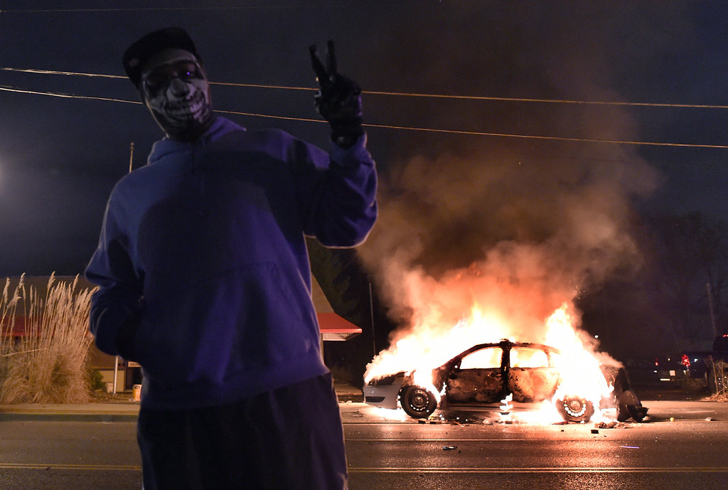 . A demonstrator flashes the victory sign before a burning police car during clashes between police and protesters over the decision in the shooting death of 18-year-old Michael Brown in Ferguson, Missouri, on November 24, 2014. US President Barack Obama urged calm as violent protests broke out on the streets of Ferguson after a grand jury decided a white policeman will not face charges for killing a black teen. AFP PHOTO/Jewel SAMAD/AFP/Getty Images