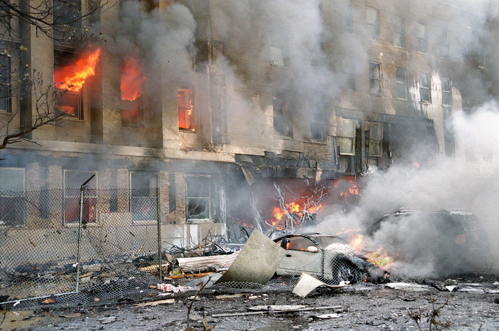 . Flames and smoke pour from a building at the Pentagon Tuesday, Sept. 11, 2001, after a direct, devastating hit from an aircraft. (AP Photo/Mandatory Credit, Will Morris)