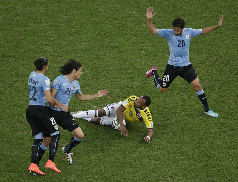 . Colombia\'s defender Juan Camilo Zuniga (C) goes to ground in front of Uruguay\'s midfielder Alvaro Gonzalez (R), Uruguay\'s defender Martin Caceres (L) and Uruguay\'s forward Edinson Cavani (2L) during the Round of 16 football match between Colombia and Uruguay at The Maracana Stadium in Rio de Janeiro on June 28, 2014, during the 2014 FIFA World Cup.  FELIPE DANA/AFP/Getty Images