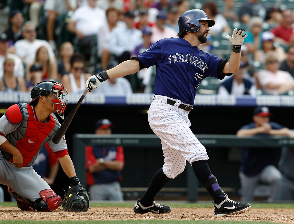 . Colorado Rockies pinch-hiter Todd Helton, right, follows the flight of his RBI-single with Washington Nationals catcher Kurt Suzuki in the ninth inning of the Nationals\' 5-4 victory in a baseball game in Denver, Thursday, June 13, 2013. (AP Photo/David Zalubowski)