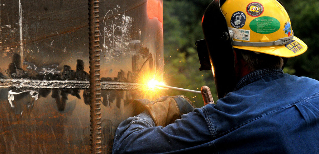 . A welder uses a torch to cut a section of a barge pier at the Xcel Dockwall that will be removed as part of the initial work to prepare for the evential placing of the footings of the new bridge on Monday afternoon July 22, 2013.  (Pioneer Press: John Doman)