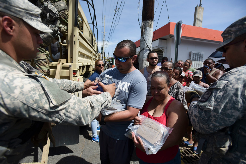 . National Guardsmen arrive at Barrio Obrero in Santurce to distribute water and food among those affected by the passage of Hurricane Maria, in San Juan, Puerto Rico, Sunday, Sept. 24, 2017. Federal aid is racing to stem a growing humanitarian crisis in towns left without fresh water, fuel, electricity or phone service by the hurricane. (AP Photo/Carlos Giusti)