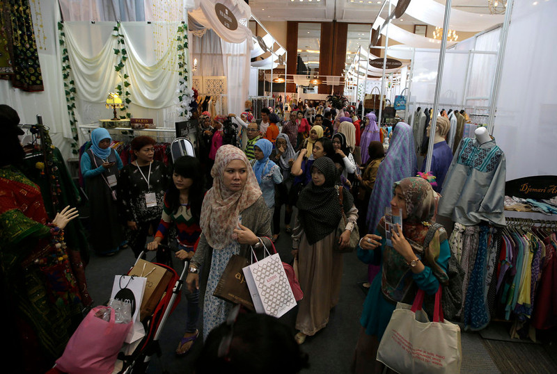 . In this Thursday, May 30, 2013 photo, Indonesian Muslim women browse exhibitors\' booths during Islamic Fashion Fair in Jakarta, Indonesia. Indonesia is the world\'s most populous Muslim country, but most people follow a moderate form of the religion. Many women wear bright and creative headscarves along with brand-name jeans and long-sleeved fitted shirts. (AP Photo/Dita Alangkara)