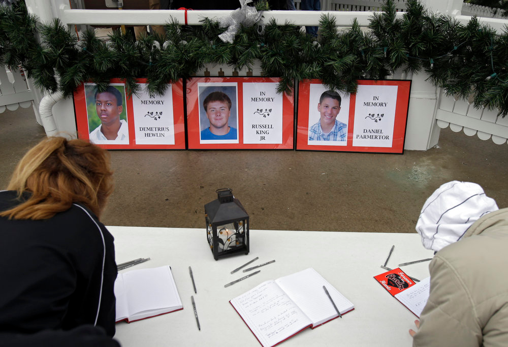 . Residents sign guest books for the families of students killed in a school shooting, at a memorial on the one-year anniversary of the shootings, in Chardon, Ohio Wednesday, Feb. 27, 2013. Students at Chardon High School walked arm-in-arm in the damp cold Wednesday afternoon from the school to the town square for a memorial commemoration. The march ended at the courthouse where 18-year-old shooter T.J. Lane pleaded guilty to all charges in February. (AP Photo/Mark Duncan)