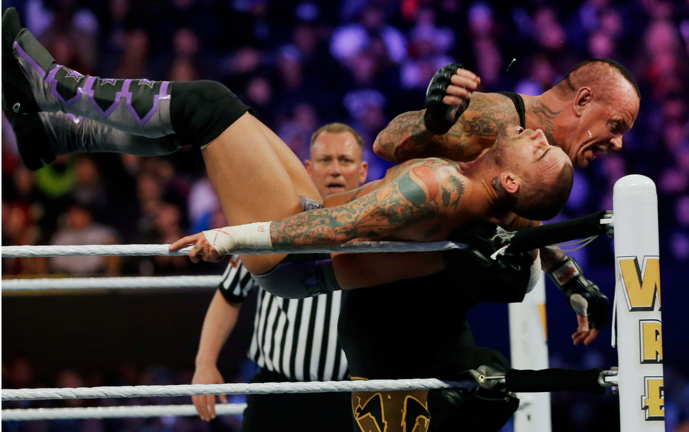 . Wrestler Mark William Calaway, known as Undertaker, right, hits Phillip Jack Brooks known as CM Punk  as they wrestle Sunday, April 7, 2013, in East Rutherford, N.J., during Wrestlemania. (AP Photo/Mel Evans)