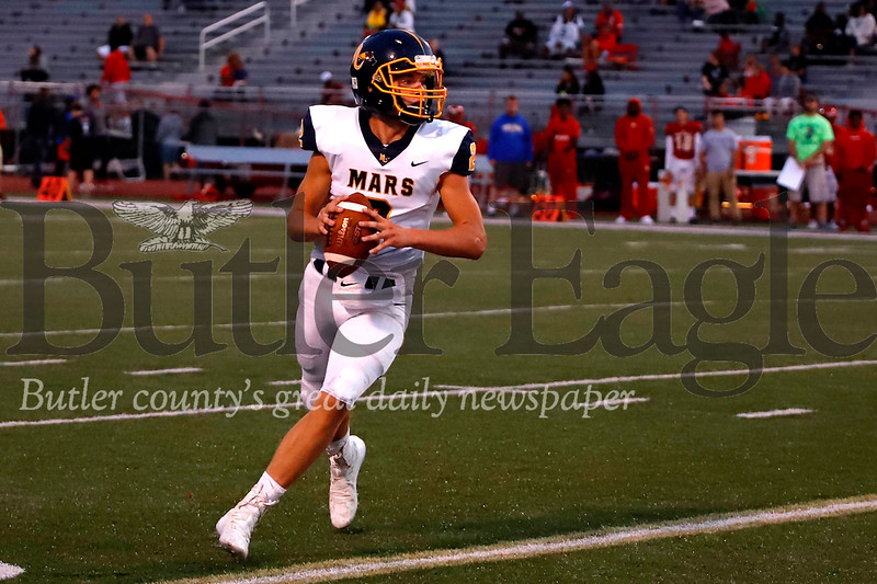 Mars quarterback Quinn Fuller rolls out of the pocket to fire a pass to Mitchell Wright for a go-ahead score against Penn Hills in the second quarter. The Planets fell to Penn Hills 14-7 after a late fourth quarter touchdown. Seb Foltz/Butler Eagle