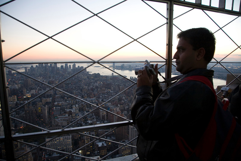 Visitor taking pictures from the top of the Empire State Building, NYC, USA