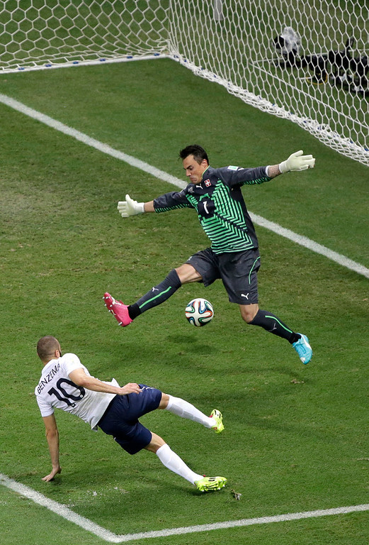 . France\'s Karim Benzema, bottom, shoots and scores his side\'s fourth goal past Switzerland\'s goalkeeper Diego Benaglio during the group E World Cup soccer match between Switzerland and France at the Arena Fonte Nova in Salvador, Brazil, Friday, June 20, 2014. (AP Photo/Sergei Grits)