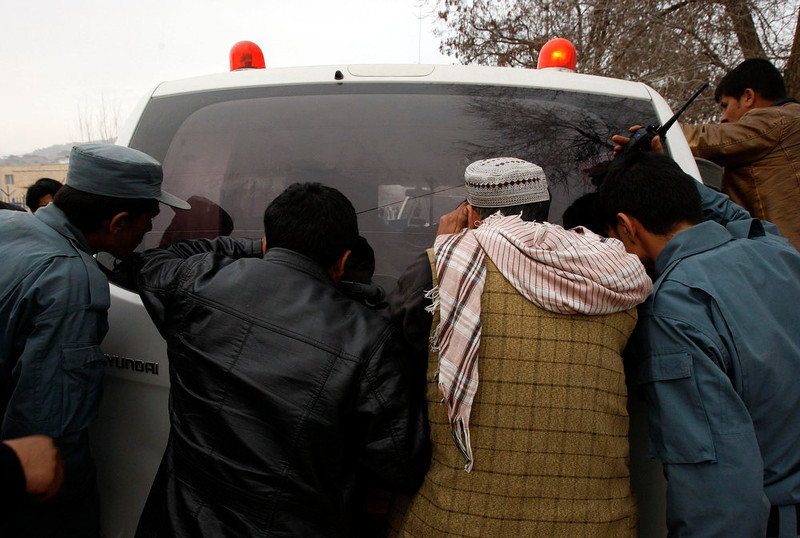 . Afghans look at the bodies of Afghan policemen inside an ambulance after they were killed in Wardak province, March 11, 2013. Two American soldiers were killed in a so-called insider attack when a person in an Afghan military uniform turned his weapon on U.S. and Afghan forces at a joint base in the restive east of the country, coalition forces said on Monday. REUTERS/ Mohammad Ishaq