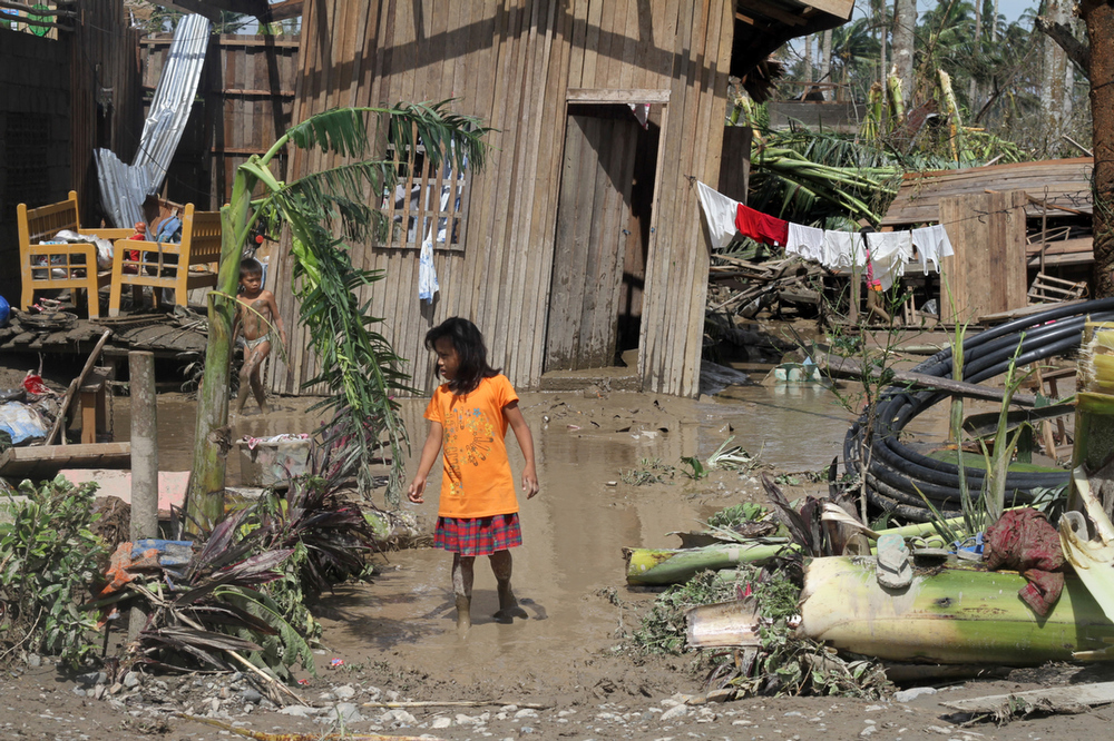 Description of . Children walk in front of their flooded home in the aftermath of Typhoon Bopha in New Bataan, Compostela Valley in the southern Philippines on December 5, 2012. The death toll from a typhoon that ravaged the Philippines jumped to 238 on December 5 with hundreds missing, as rescuers battled to reach areas cut off by floods and mudslides, officials said. KARLOS MANLUPIG/AFP/Getty Images