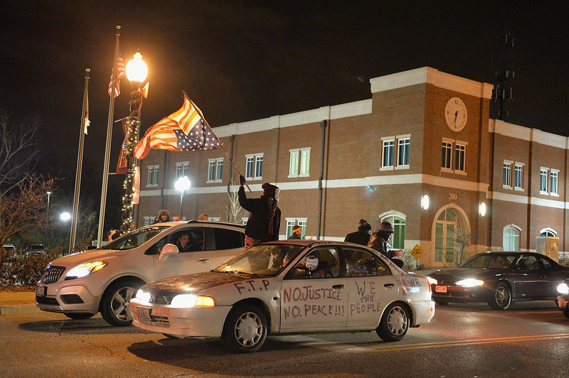 . A demonstrator waves an American flag as a car drives down the street outside the Ferguson Police Department in Ferguson Missouri, on November 24, 2014 as demonstrators protest the death of 18-year-old unarmed black teenager Michael Brown, who was shot to death by a white police officer.  The governor of the US state of Missouri urged calm on November 24th ahead of a verdict on whether to indict officer Darren Wilson for shooting dead unarmed Brown. There is no indication yet as to whether or not Wilson will face charges for the death of Brown on August 9, 2014 in Ferguson, a suburb just outside St Louis. The grand jury announcement will be made at the Buzz Westfall Justice Center in Clayton, Missouri, at 8:00 pm (0200 GMT Tuesday), St Louis County prosecutors said. Michael B. Thomas/AFP/Getty Images