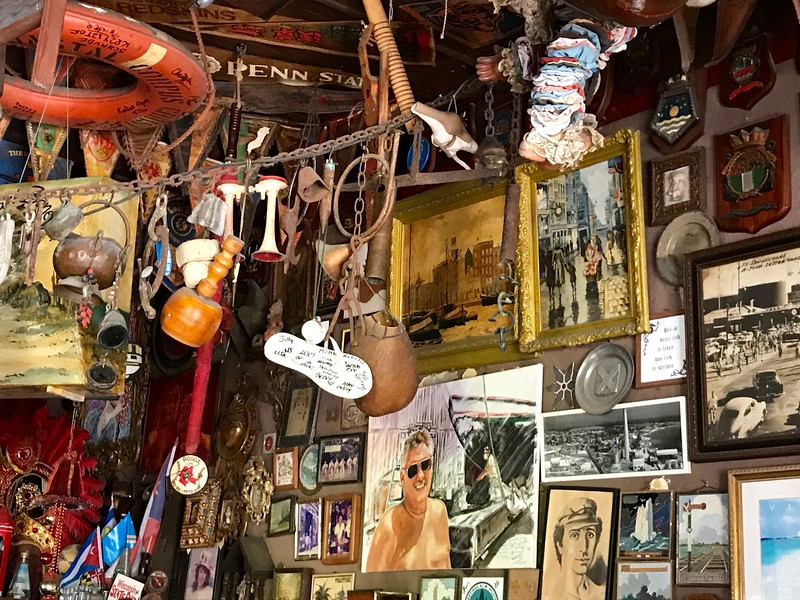 walls of a bar filled with painting and memorabilia