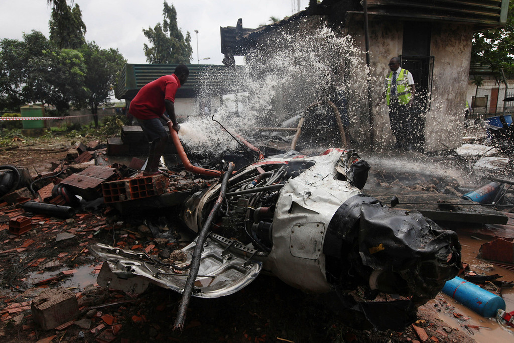 . A rescue worker douses a part of the wreckage of a charter passenger jet which crashed soon after take off from Lagos airport, Nigeria, Thursday, Oct. 3, 2013.  (AP Photo/Sunday Alamba)