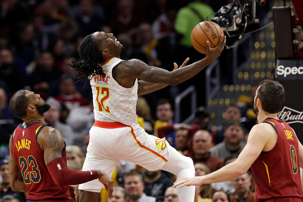 . Atlanta Hawks\' Taurean Prince, center, drives to the basket between Cleveland Cavaliers\' LeBron James, left, and Kevin Love in the second half of an NBA basketball game, Tuesday, Dec. 12, 2017, in Cleveland. The Cavaliers won 123-114. (AP Photo/Tony Dejak)