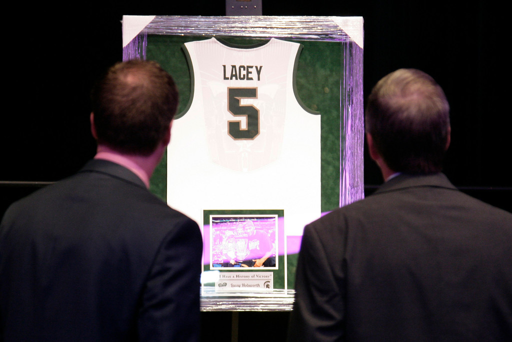. Attendees look at a Michigan State basketball jersey before a memorial to celebrate the life and legacy of Lacey Holsworth, an 8-year-old Michigan State basketball fan whose battle with cancer inspired the team\'s players, coaches and many more beyond the hardwood, Thursday, April 17, 2014, at Michigan State University\'s Breslin Center in East Lansing, Mich. (AP Photo/Al Goldis)