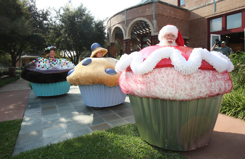 Description of . Brady White as Santa Claus drives a Customized Cupcake Car with Lisa Pongrace, and Greg Solberg, rear, at the unveiling of luxury retailer Neiman Marcus' Christmas Book Tuesday, Oct. 6, 2009, in Dallas. The cars are powered by a 24-volt electric motor and cost $25K.  (AP Photo/Tim Sharp)