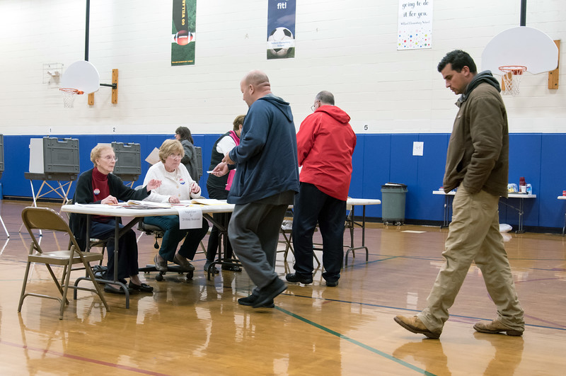 11/06/18  Wesley Bunnell | Staff  Luis Cancel, middle, is greeted by checkers Irene Fiori and Elaine Borselle while checking into vote at the Willard Elementary School on Tuesday night as Matt Currao waits his turn.