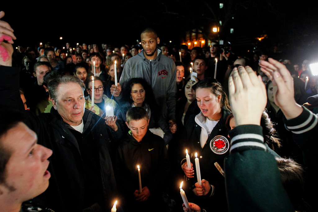 . Michigan State men\'s basketball coach Tom Izzo, second from left; his son Steven, middle front; his wife, Lupe, behind Steven; MSU basketball player Adreian Payne, behind Lupe Izzo; and others sing during a candelight vigil along the banks of the Red Cedar River on the MSU campus Wednesday, April 9, 2014, in East Lansing, Mich., in memory of Lacey Holsworth, of St. Johns, Mich. Eight-year-old Lacey died Tuesday night of cancer. (AP Photo/Lansina State Journal, Matthew Dae Smith) NO SALES