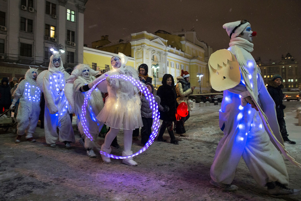 . People dressed in illuminated angel costumes parade to mark Christmas Day in central Moscow, Russia, on Thursday, Dec. 25, 2014. (AP Photo/Pavel Golovkin)