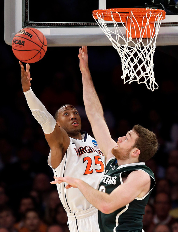 . Virginia forward Akil Mitchell, left, goes up for a shot against Michigan State forward Matt Costello during the first half in a regional semifinal of the NCAA men\'s college basketball tournament, Friday, March 28, 2014, in New York. (AP Photo/Seth Wenig)