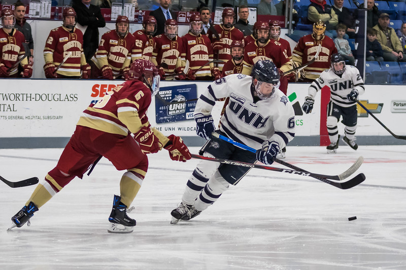 UNH's Angus Crookshank (6) moves the puck as BC's Ben Finkelstein (6) defends during Hockey East action Saturday night in Durham. [Scott Patterson/Fosters.com]